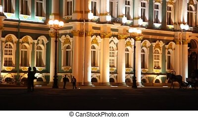 Horses harnessed go to carriage on Palace Square in front of facade Hermitage