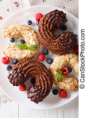 Horseshoe biscuits with chocolate and almonds close-up on a plate. vertical top view