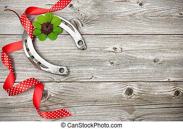 Horseshoe, shamrock and red ribbon on old wooden - Holidays...