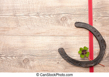 horseshoes with four leaf clover over wooden background