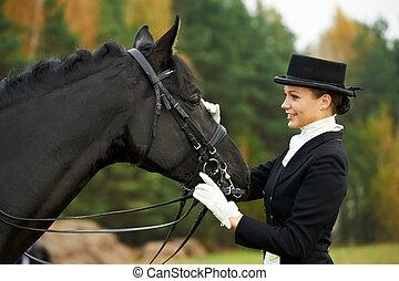 horsewoman jockey in uniform with horse - horsewoman jockey...