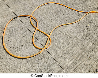 Hose for water lying on a concrete slab in the street. Material for repairs in an apartment is under construction