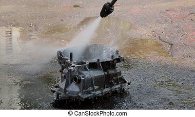 Hose washing a large metal part. washing gearbox....