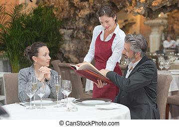 hospitable waitress taking couples order in gastronomy restaurant