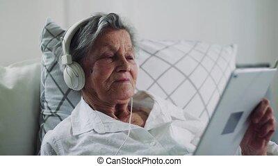 hospital., femme, tablette, écouteurs, lit, malade, maison, personne agee, ou, mensonge