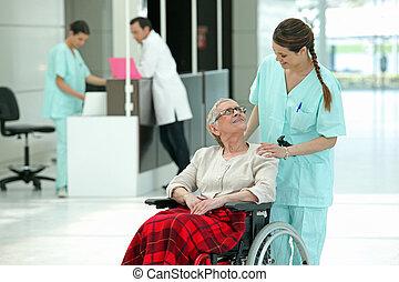 Hospital nurse pushing an elderly lady in a wheelchair