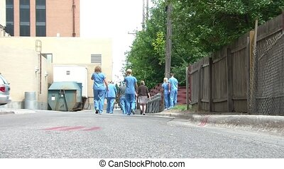 Hospital Staff Walking Down Alleyway