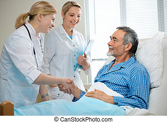 hospital  - doctor shakes hands with patient in hospital bed