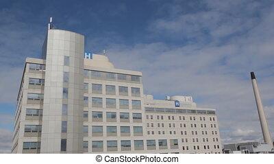Hospital w/ timelapse clouds. Wide. - Hospital with blue sky...
