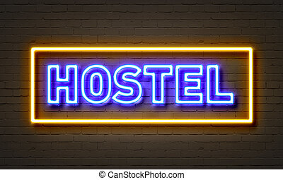 Hostel neon sign on brick wall background.