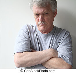 hostile senior man - angry older man with his arms crossed
