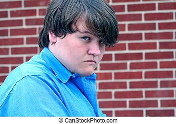 Portrait of a teenage boy with a hostile expression, with a brick background. Taken outdoors.