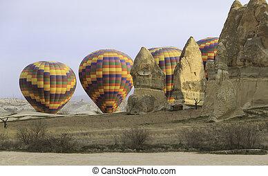 Hot Air balloon behind rocks in the desert