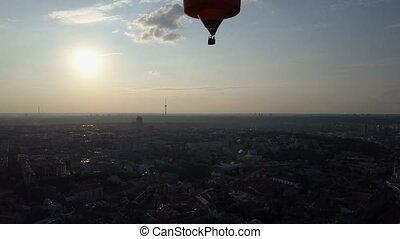 Hot air balloon floating over city at dawn, sun rising on horizon, aspirations