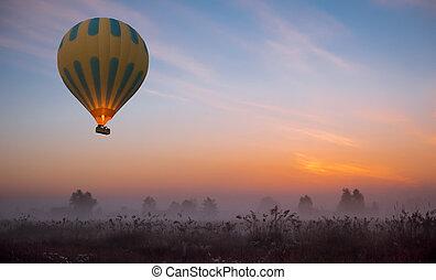 hot air balloon flying at yellow sunrise