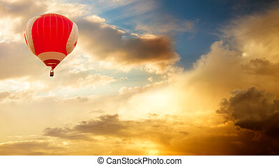 Hot Air Balloon Flying over Golden Sunset Sky