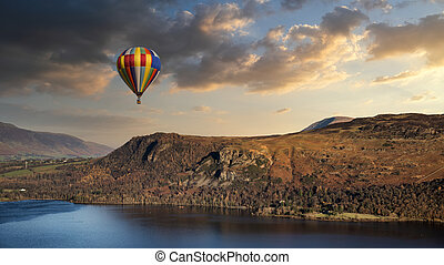 Hot air balloon flying over stunning Derwentwater landscape in Lake District during Summer dunset