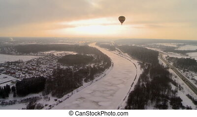 Hot air balloon flying over winter landscape