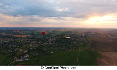 Hot air balloon in the sky over a field. - Red balloon in...