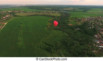 Hot air balloon in the sky over a field.Aerial view - Red...