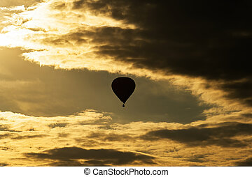 Hot air balloon on evening sky with clouds