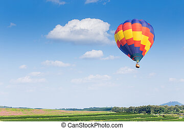 Hot air balloon over green fields