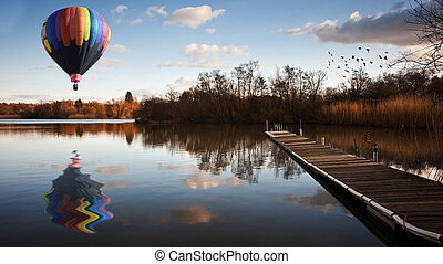 Hot air balloon over sunset lake with jetty