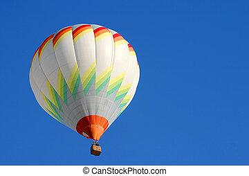 Hot air balloon in flight isolated on blue sky