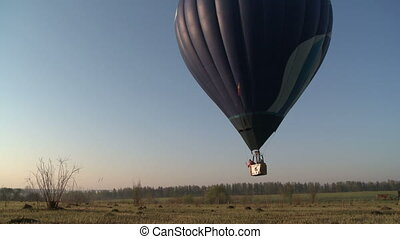 Hot air balloon rising above the ground view