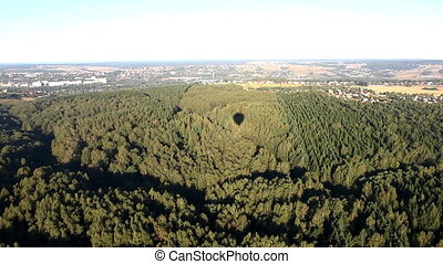 Hot air balloon shadow on morning forest