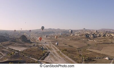 Hot air balloons flying over Goreme village. Cappadocia, Turkey. View from above.