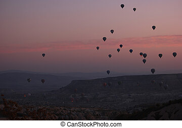 Hot air balloons flying over rocky landscape at sunset sky.
