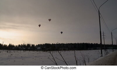 Hot air balloons flying over snow-covered field