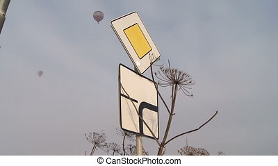 Hot air balloons flying over traffic signs