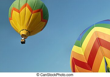 Hot air balloon soaring against immaculate blue sky with a second one partially in the corner. Bright colors.