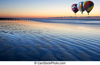 Beautiful low point of view along beach at low tide out to sea with vibrant sunrise sky with hot air balloons over sea
