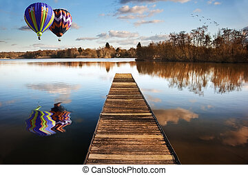 Hot air balloons over sunset lake with jetty