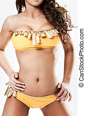 Hot babe in yellow bikini  suite standing isolated