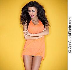 Hot beautiful brunette posing in an orange dress
