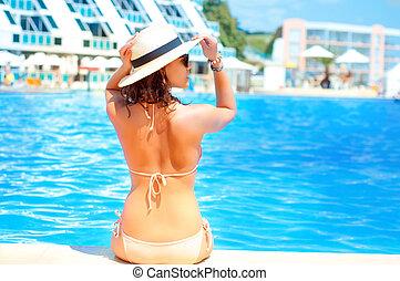 Hot beautiful woman in hat and bikini standing