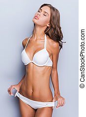 Hot beauty. Attractive young brown hair woman in white lingerie stretching her panties and keeping eyes closed while standing against grey background and smiling