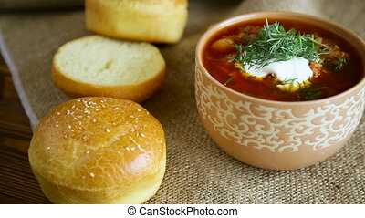 hot beetroot soup with sour cream, herbs and rolls in a ...