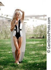 Hot blonde woman standing with a wakeboard on green grass