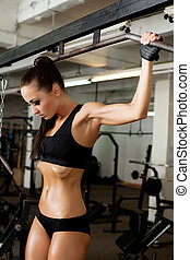 Hot brunette pulls on crossbeam in gym