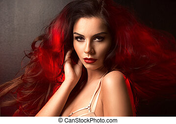 Hot brunette woman in red light on hair