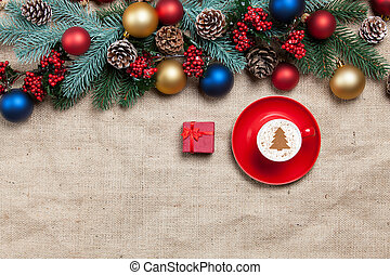 Hot cappuccino with christmas tree shape and gift box on a table