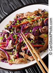 Hot chinese pork moo shu with vegetables close-up in a plate...