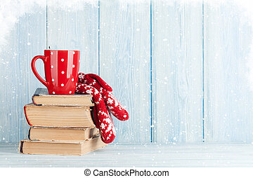 Hot chocolate cup and mittens over books. Christmas. View...
