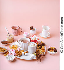 Hot chocolate drink in mugs, sweets assortment of marshmallows, chocolates and cookies on pink background