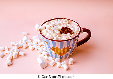 Hot chocolate drink with marshmallows and chocolate crisp in blue striped mug on pastel pink background